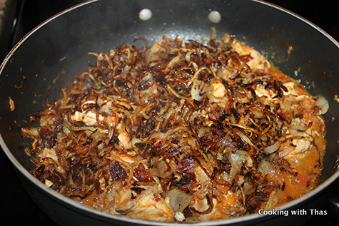 adding fried onions to chicken
