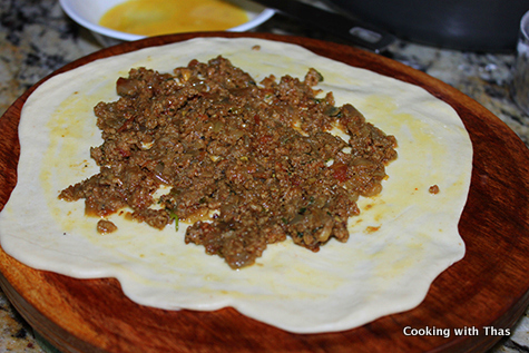 spread ground beef masala on dough